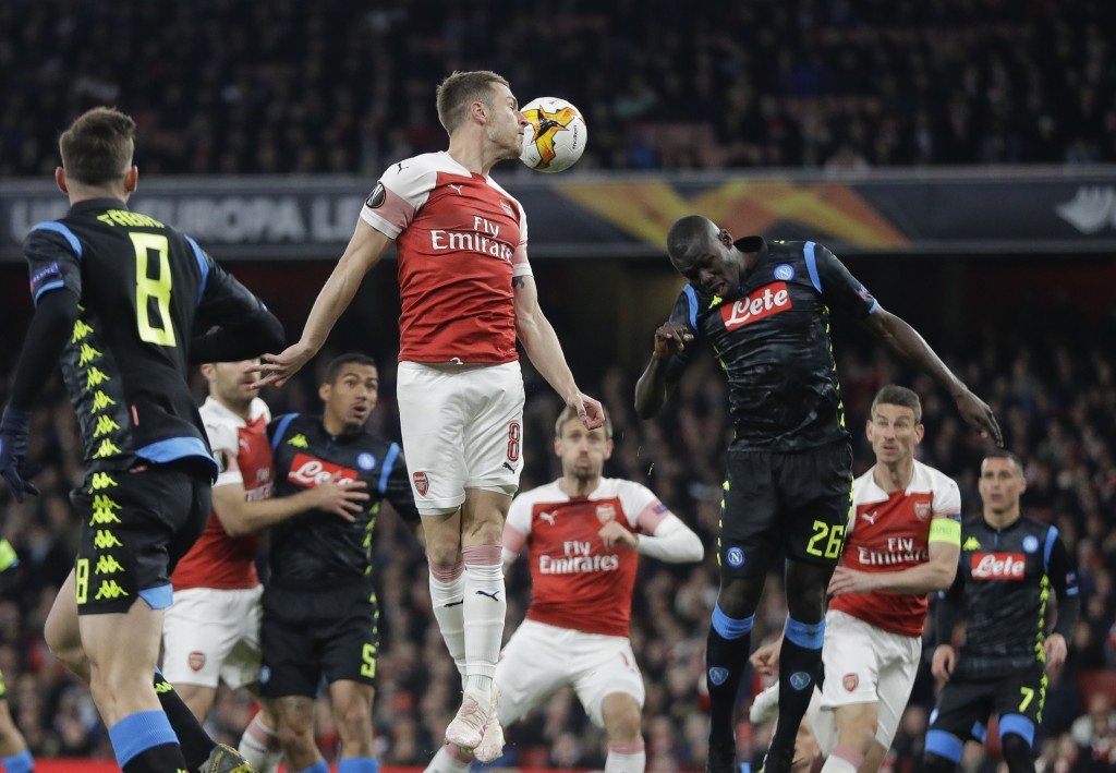 Arsenal's Aaron Ramsey, left, jumps for a header with Napoli's Kalidou Koulibaly during the Europa League first leg quarterfinal soccer match between