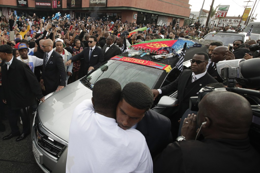 Two men hug as a hearse carrying the casket of slain rapper Nipsey Hussle passes through the crowd Thursday, April 11, 2019, in Los Angeles. The 25-mi