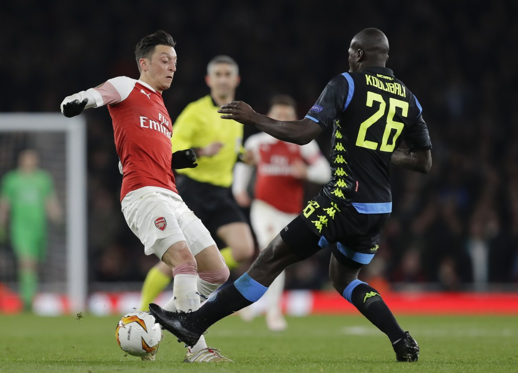 Arsenal's Mesut Ozil, left, challenges for the ball with Napoli's Kalidou Koulibaly during the Europa League first leg quarterfinal soccer match betwe