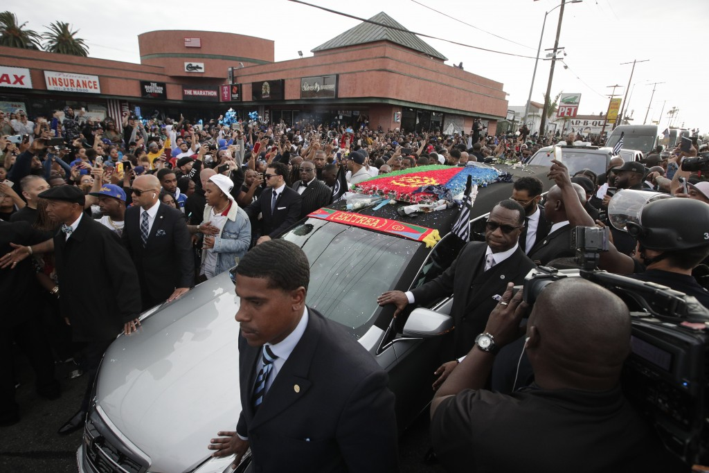 People watch as a hearse carrying the casket of slain rapper Nipsey Hussle passes Hussle's clothing store The Marathon, Thursday, April 11, 2019, in L