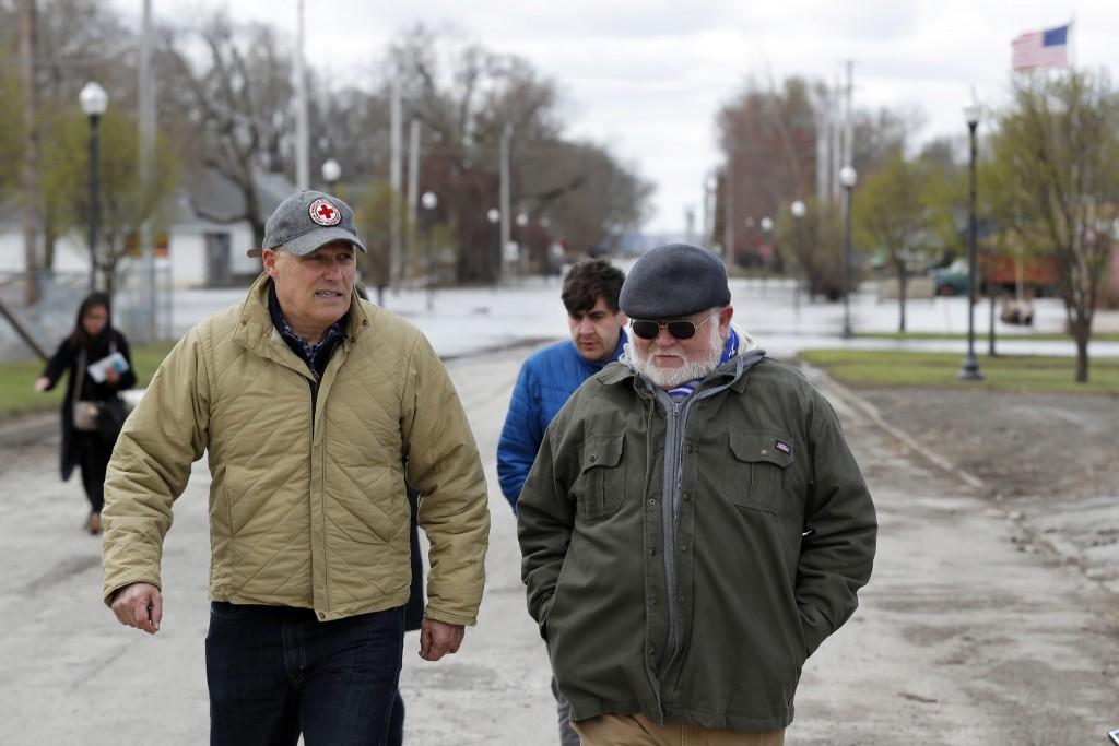 2020 Democratic presidential candidate Washington Gov. Jay Inslee, left, walks with climate analyst John Davis, of Hamburg, Iowa, while touring flood