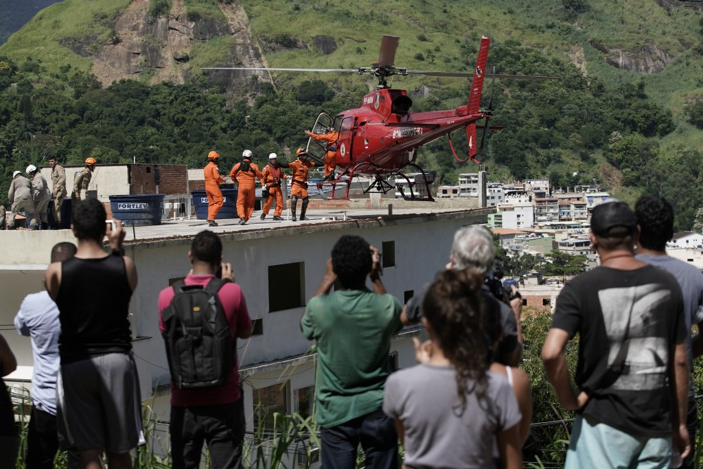 Residents watch as a helicopter prepares to take off carrying an injured woman rescued from the rubble of two buildings that collapsed in the Muzema n