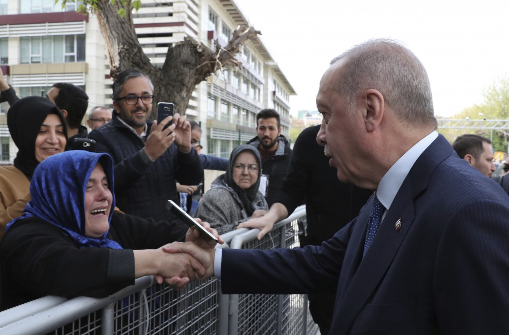 Turkey's President Recep Tayyip Erdogan shakes hands with a supporter as he arrives to speak at an assembly for religious schools, in Istanbul, Saturd