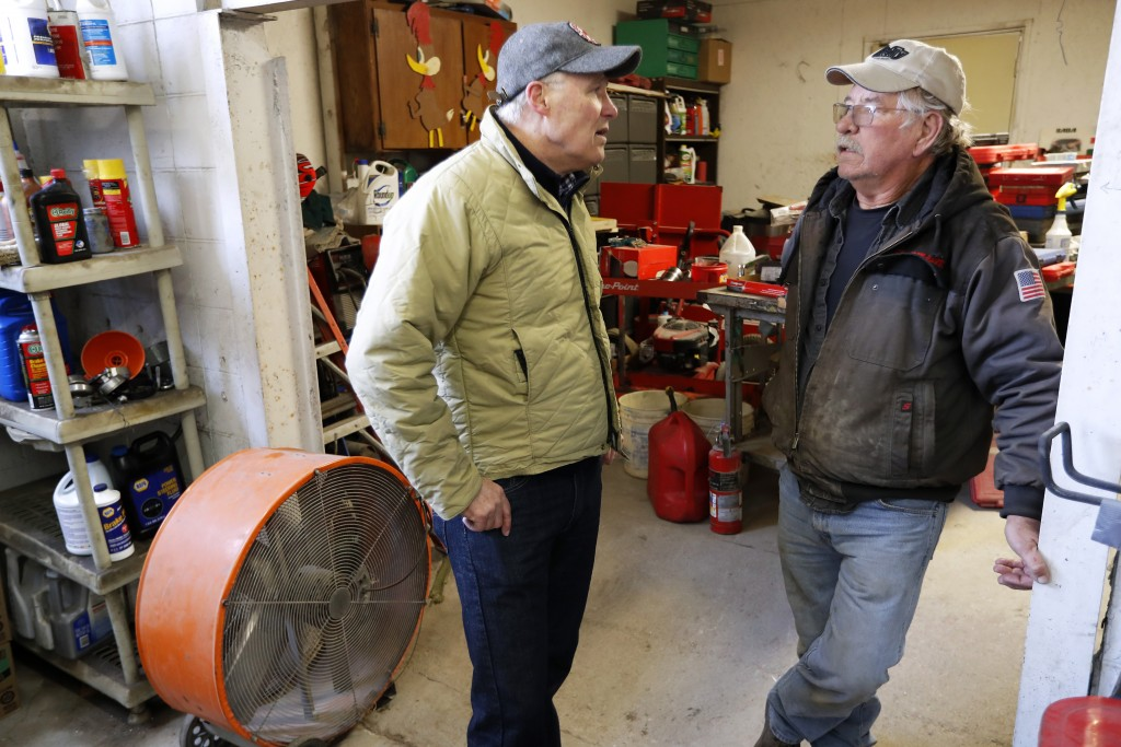 2020 Democratic presidential candidate Washington Gov. Jay Inslee talks with Ron Perry, of Hamburg, Iowa, right, while touring flood damage, Friday, A...