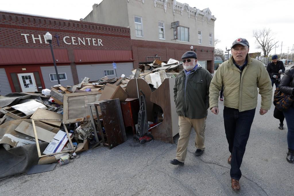 2020 Democratic presidential candidate Washington Gov. Jay Inslee, right, walks with climate analyst John Davis, of Hamburg, Iowa, while touring flood
