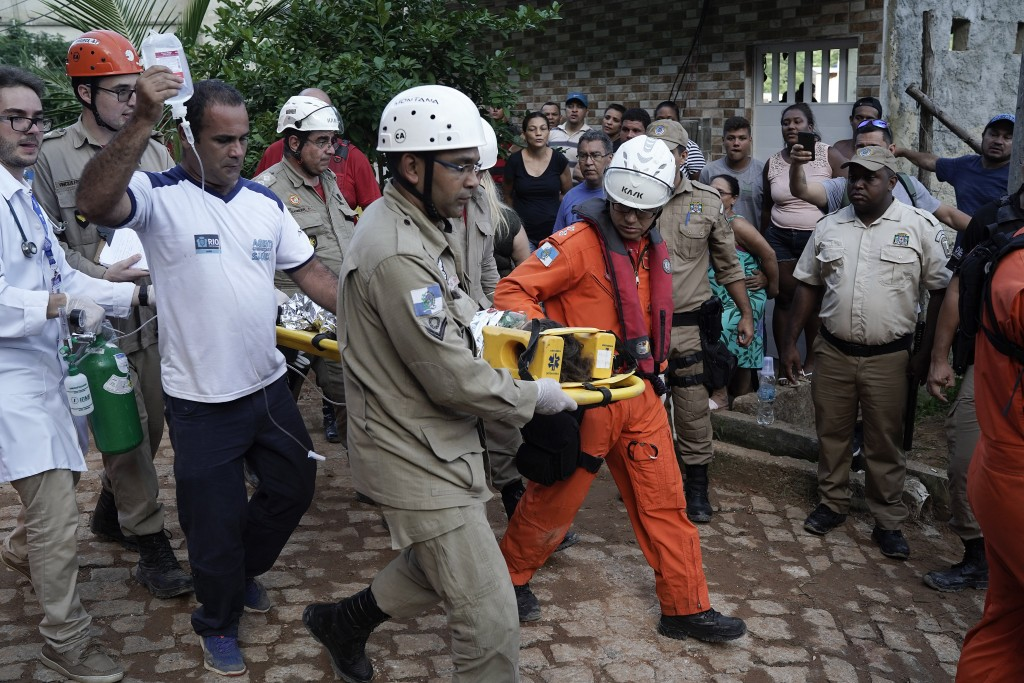 Firefighters accompany an injured child who was rescued from the rubble of two buildings that collapsed in the Muzema neighborhood, in Rio de Janeiro,