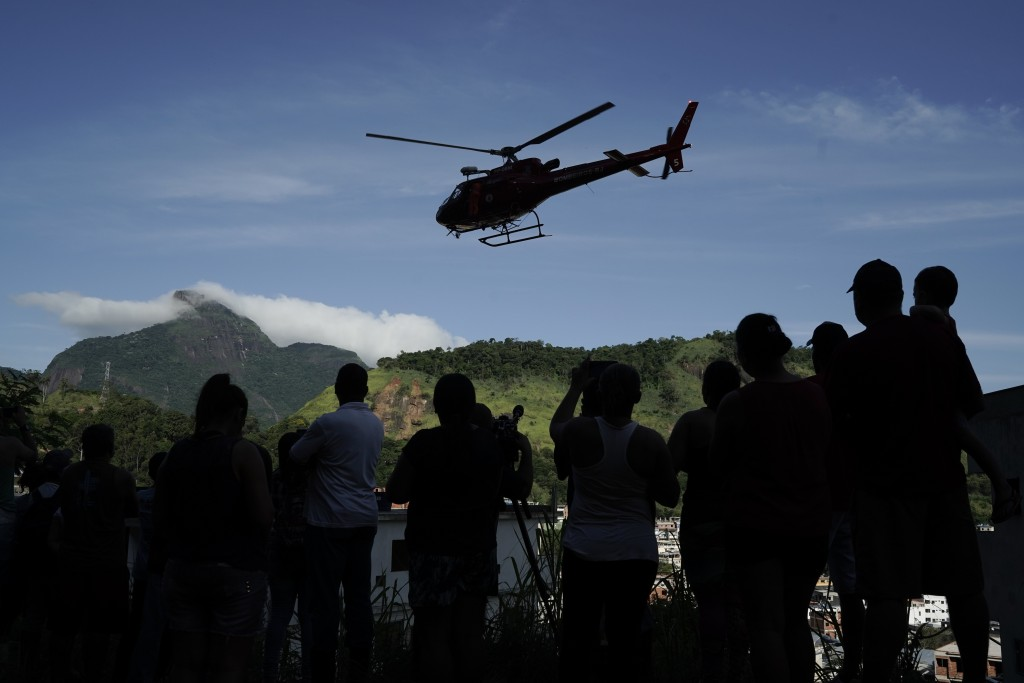 Residents watch a helicopter fly past transporting an injured person who was rescued from the rubble of two buildings that collapsed in the Muzema nei