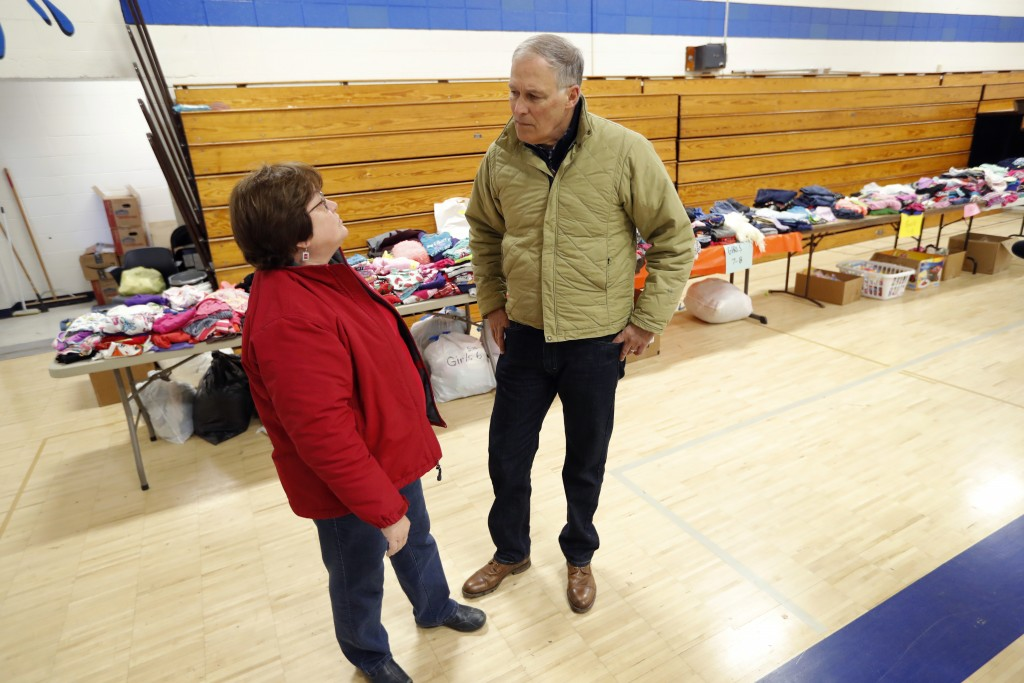 2020 Democratic presidential candidate Washington Gov. Jay Inslee talks with Sandra McKinnon, left, while visiting a flood service support center, Fri