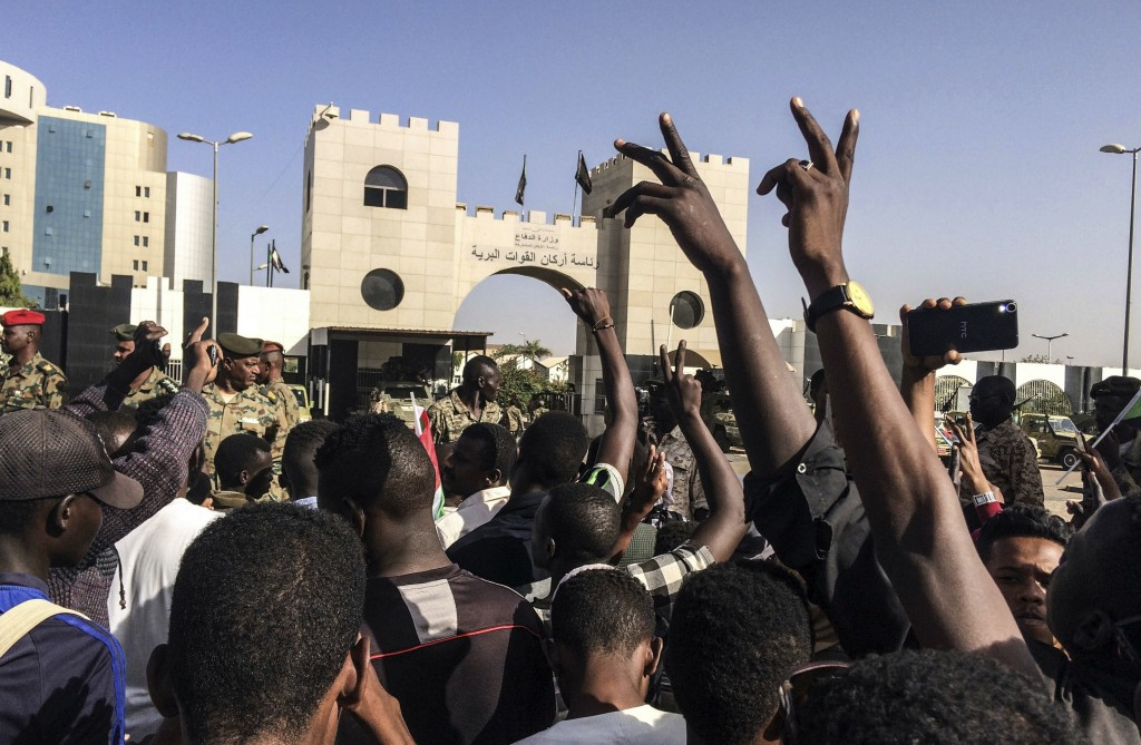Sudanese demonstrators march with national flags as they gather during a rally demanding a civilian body to lead the transition to democracy, outside