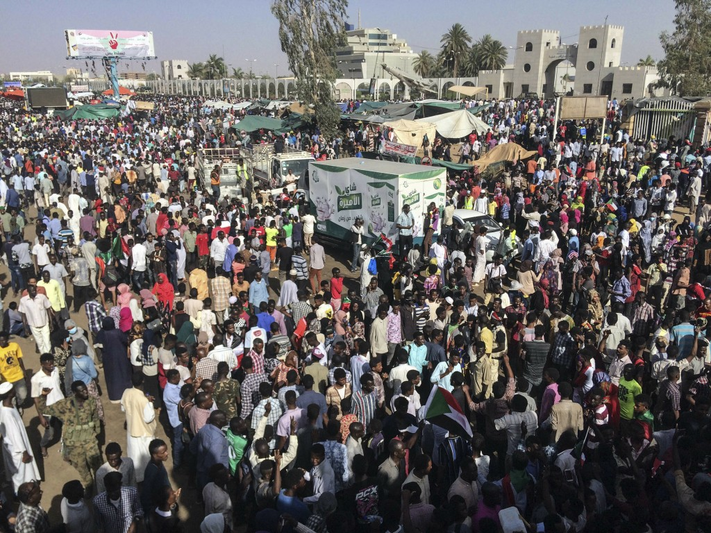 Sudanese demonstrators march with national flags as they gather during a rally demanding a civilian body to lead the transition to democracy, outside ...