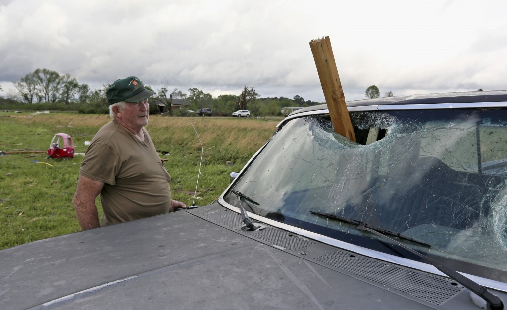 A man looks at a piece of wood that was blown through the windshield of his daughters truck in Hamilton, Miss., after a storm moved through the area S...