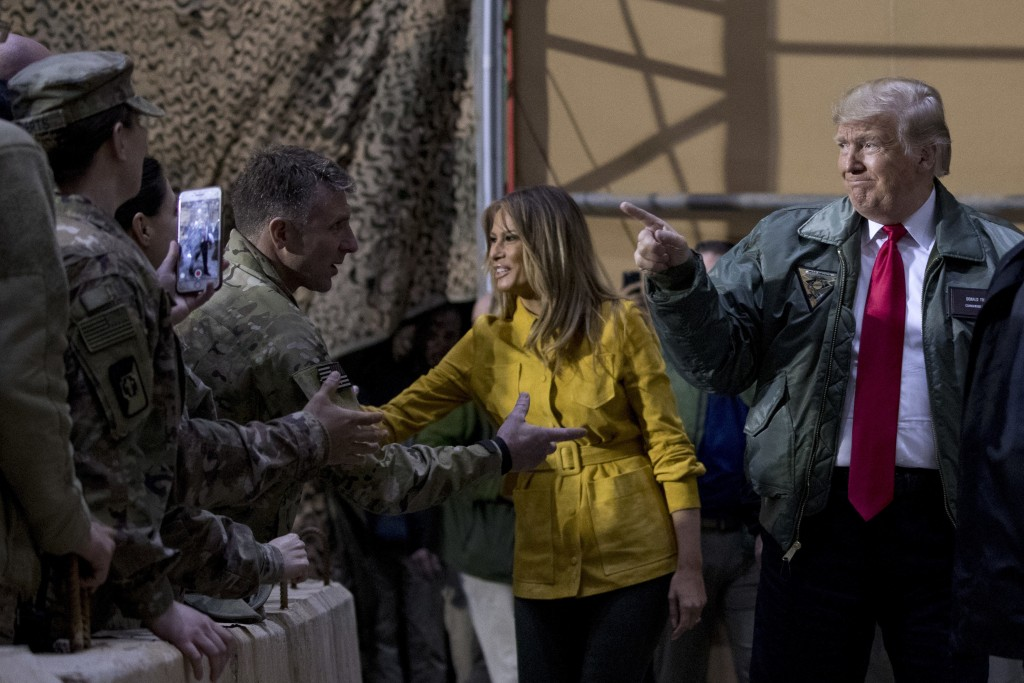 FILE -- In this Dec. 26, 2018 file photo, President Donald Trump and first lady Melania Trump greet members of the military at a hangar rally at Al As...