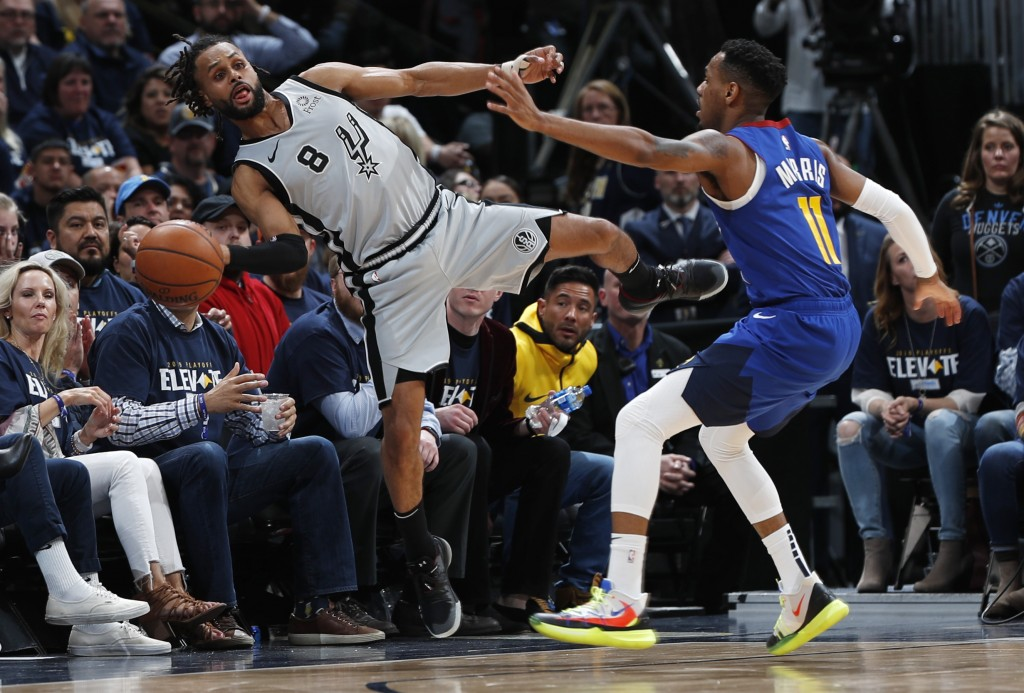 San Antonio Spurs guard Patty Mills, left, reaches out to save a ball from going out of bounds as Denver Nuggets guard Monte Morris defends in the sec