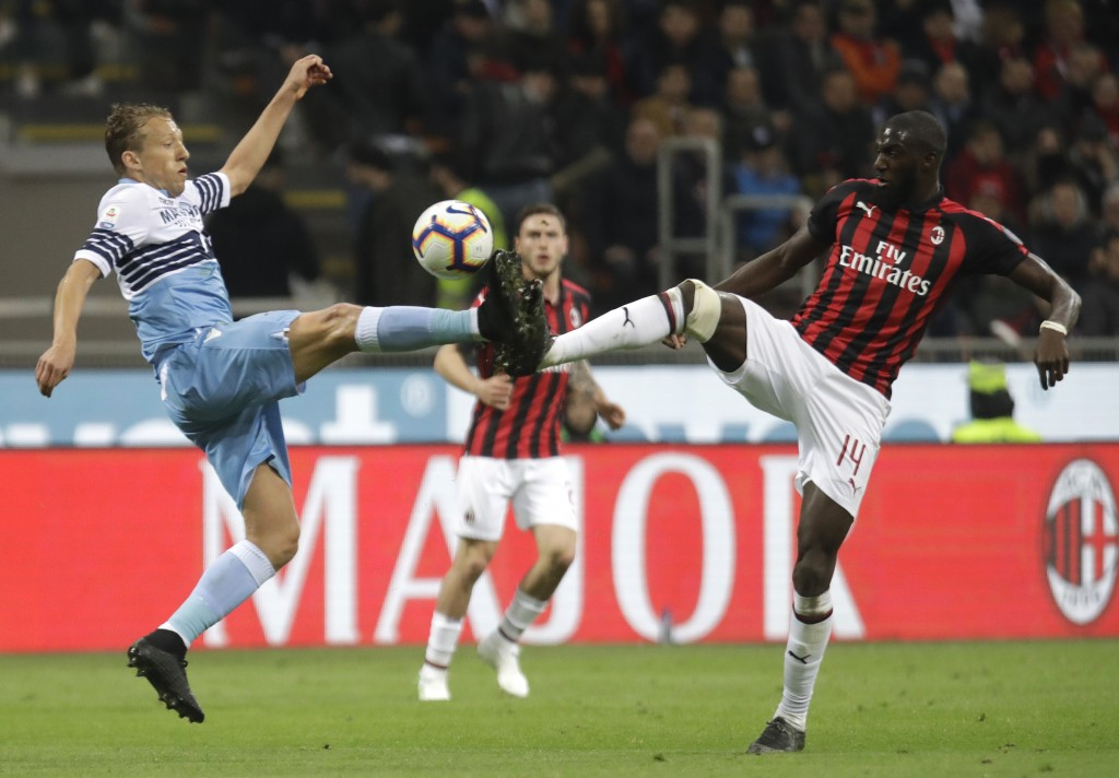 Lazio's Lucas Leiva, left, and AC Milan's Tiemoue Bakayoko challenge for the ball during the Serie A soccer match between AC Milan and Lazio, at the S...