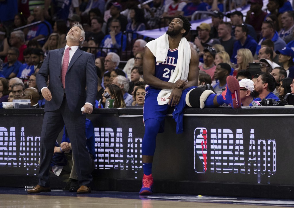 Philadelphia 76ers head coach Brett Brown, left, and Joel Embiid, right, of Cameroon, look up at the scoreboard during the first half in Game 1 of a f