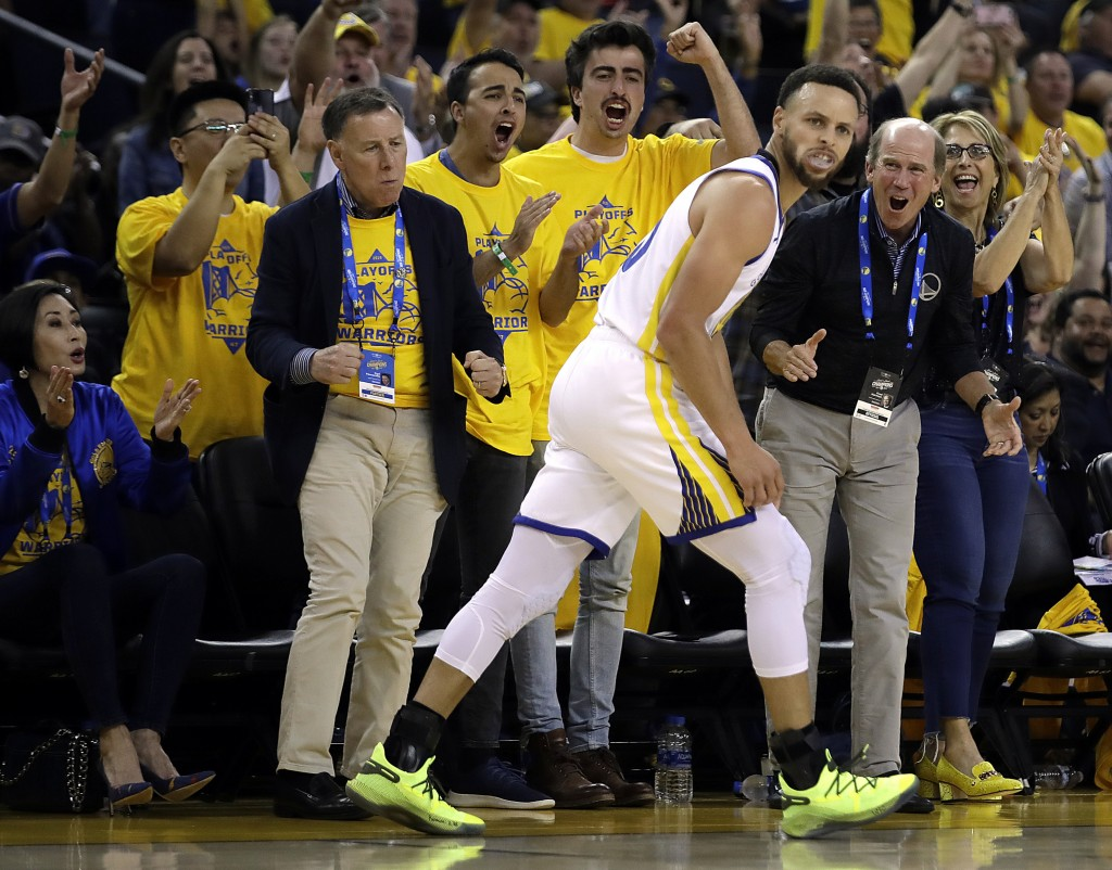 Fans cheer Golden State Warriors' Stephen Curry, front, reacts after a basket against the Los Angeles Clippers in the second half in Game 1 of a first