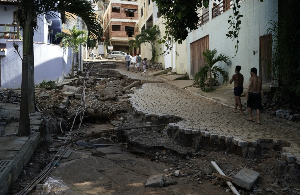 People walk on a damaged street due the heavy rain and next to the site where two buildings collapsed in Muzema neighborhood in Rio de Janeiro, Brazil