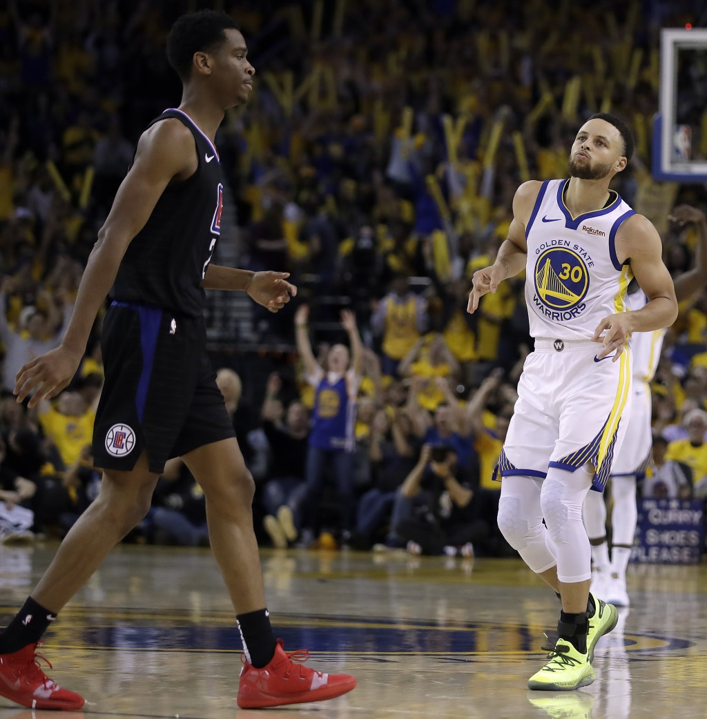 Golden State Warriors' Stephen Curry, right, celebrates after scoring in front of Los Angeles Clippers' Shai Gilgeous-Alexander during the second half