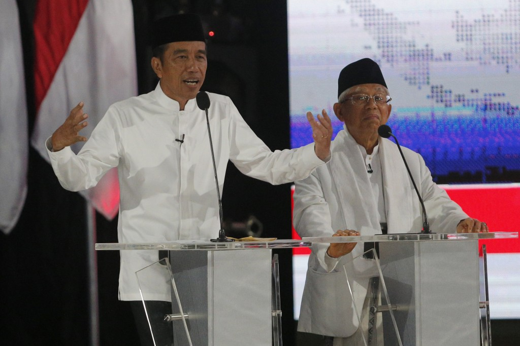 In this Saturday, April 13, 2019, file photo, Indonesian President Joko Widodo, left, delivers a speech with running mate Ma'ruf Amin, right, during a