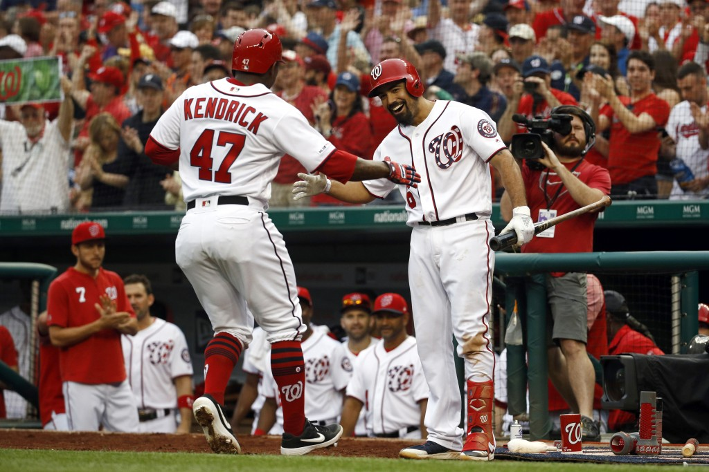 Washington Nationals' Anthony Rendon, right, greets teammate Howie Kendrick after Kendrick hit a solo home run in the eighth inning of a baseball game...