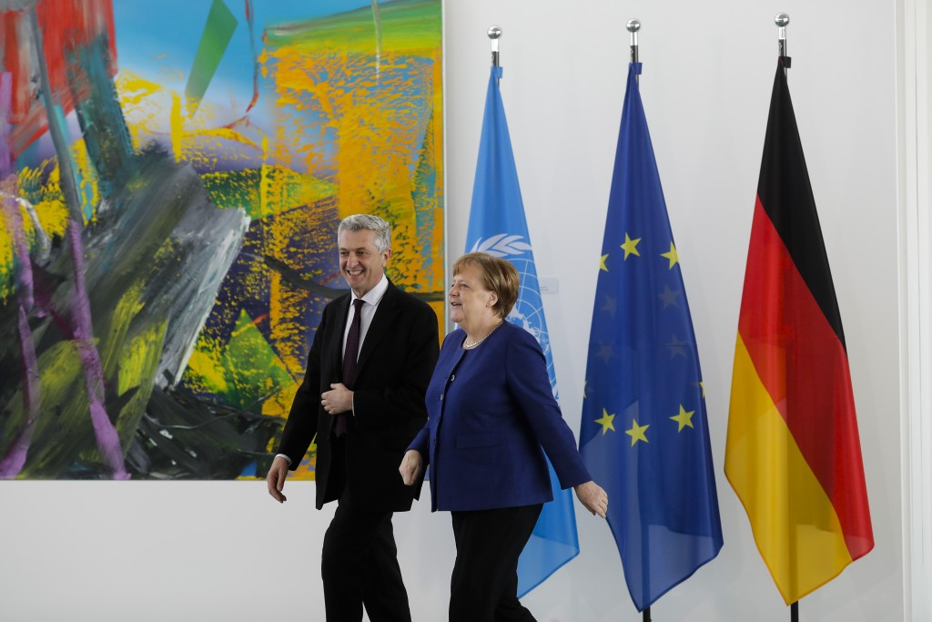 German Chancellor Angela Merkel, right, welcomes United Nations High Commissioner for Refugees Filippo Grandi, left, for a meeting at the chancellery
