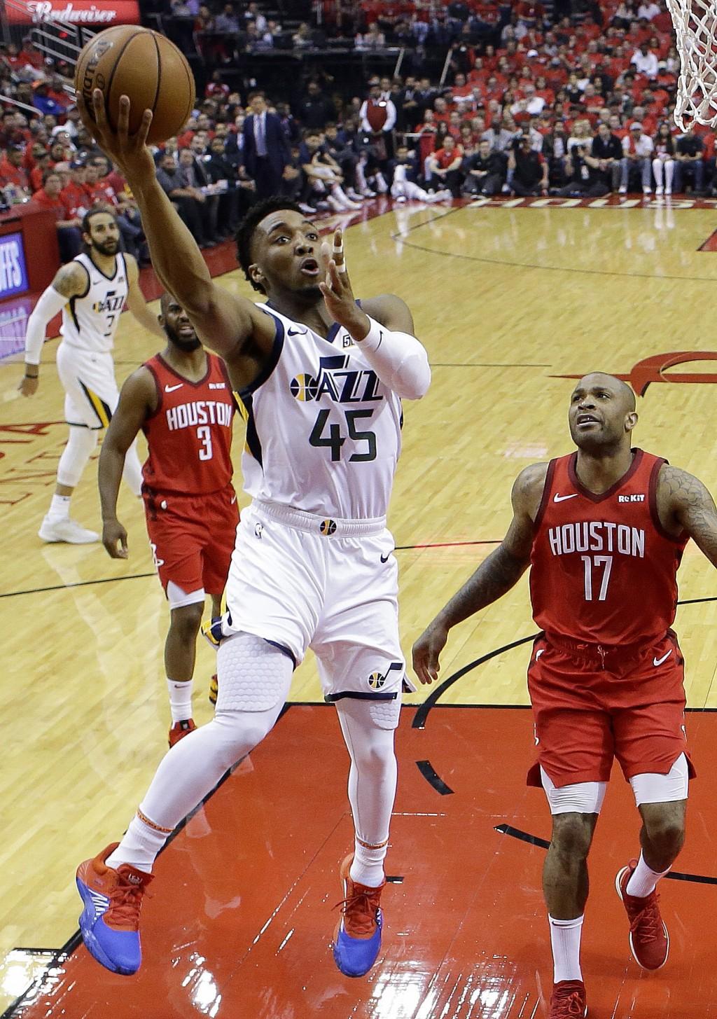 Utah Jazz guard Donovan Mitchell (45) shoots as Houston Rockets forward PJ Tucker (17) watches during the first half of Game 1 of an NBA basketball fi