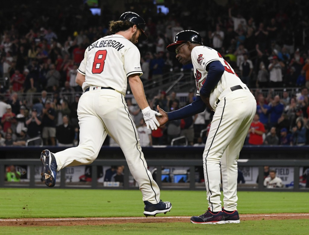 Atlanta Braves' Charlie Culberson (8) is congratulated by third base coach Ron Washington as he runs bases on his home run during the sixth inning of