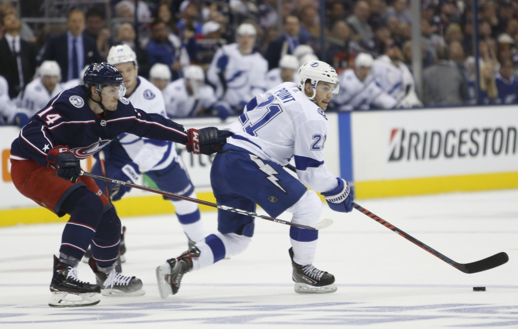 Tampa Bay Lightning's Brayden Point, right, looks for an open pass as Columbus Blue Jackets' Dean Kukan, of Switzerland, defends during the first peri