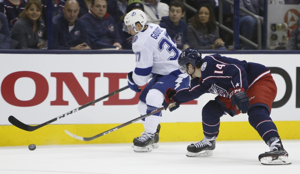 Tampa Bay Lightning's Yanni Gourde, left, carries the puck upice against Columbus Blue Jackets' Dean Kukan, of Switzerland, during the first period of