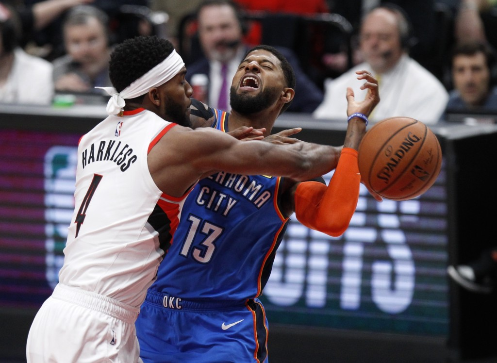 Portland Trail Blazers forward Maurice Harkless, left, knocks the ball away from Oklahoma City Thunder forward Paul George, right, during the first ha