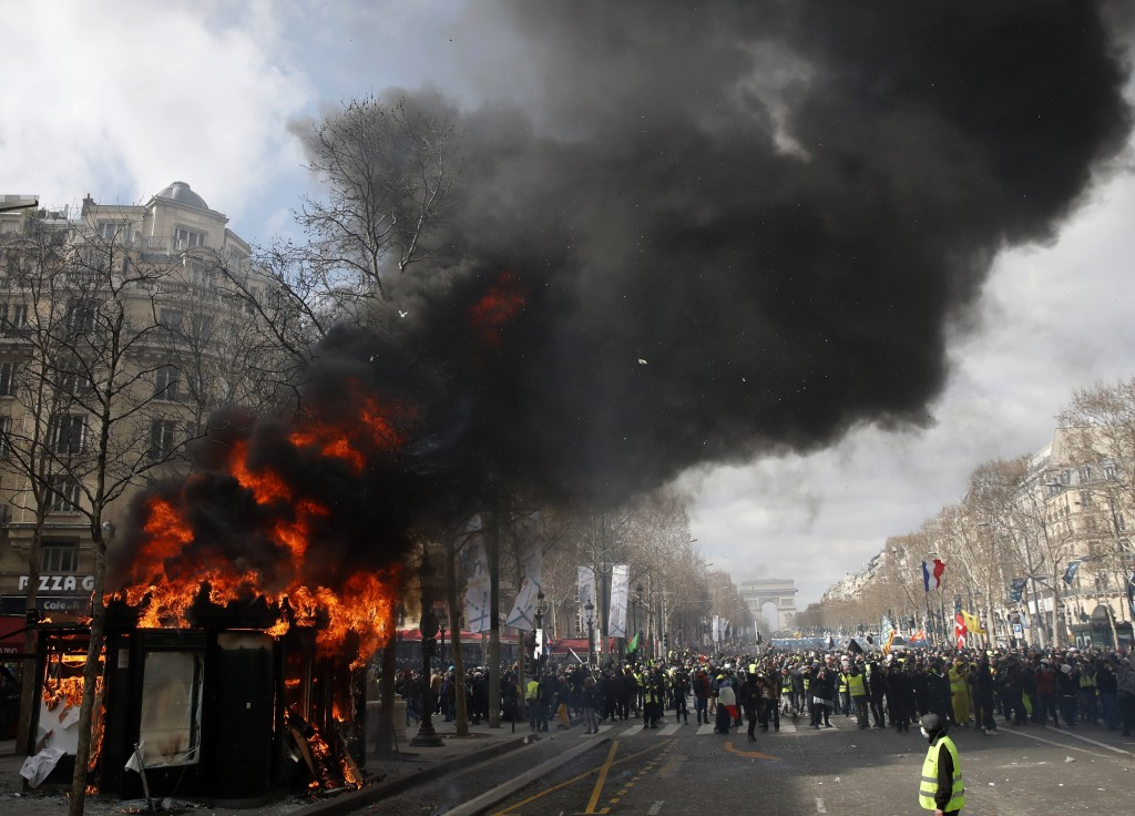 FILE - In this March 16, 2019 file photo, a news stand burns during a yellow vests demonstration on the Champs Elysees avenue in Paris. French Preside