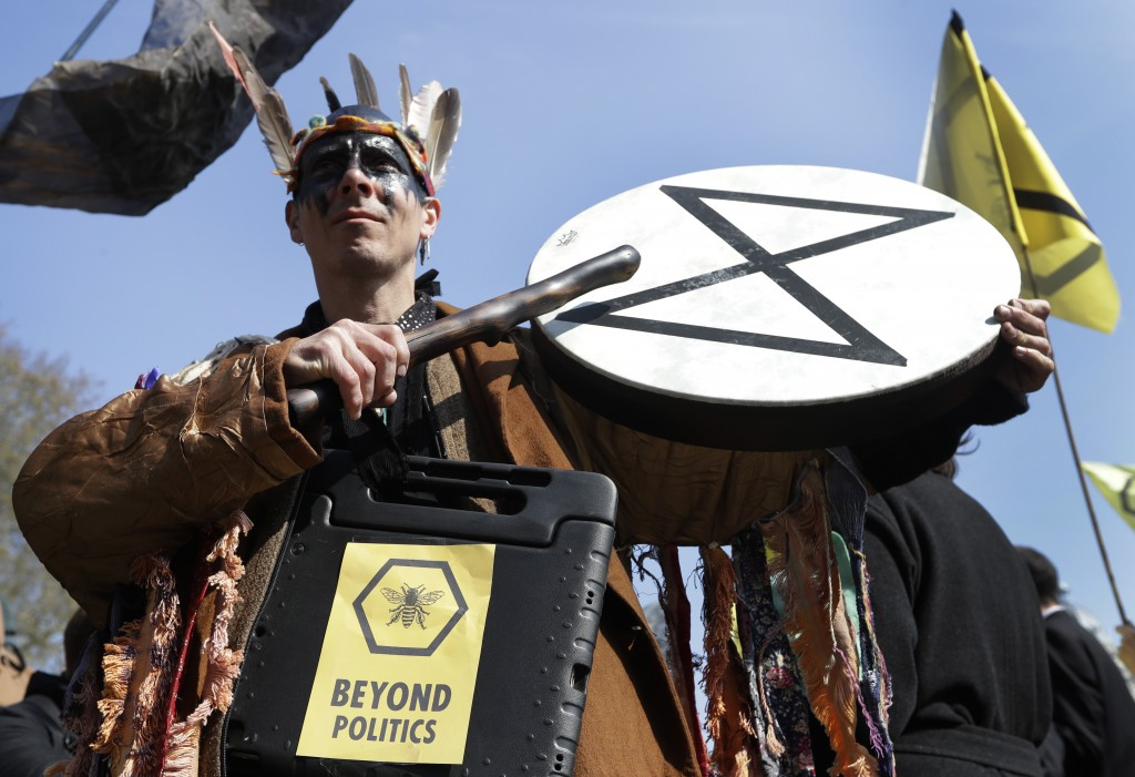A demonstrator bangs a drum during a climate protest in Parliament Square in London, Monday, April 15, 2019. Extinction Rebellion have organised a nat...