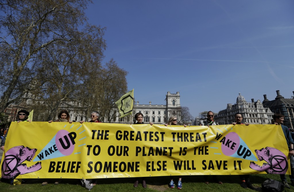 Demonstrators hold a banner during a climate protest in Parliament Square in London, Monday, April 15, 2019. Extinction Rebellion have organised a nat