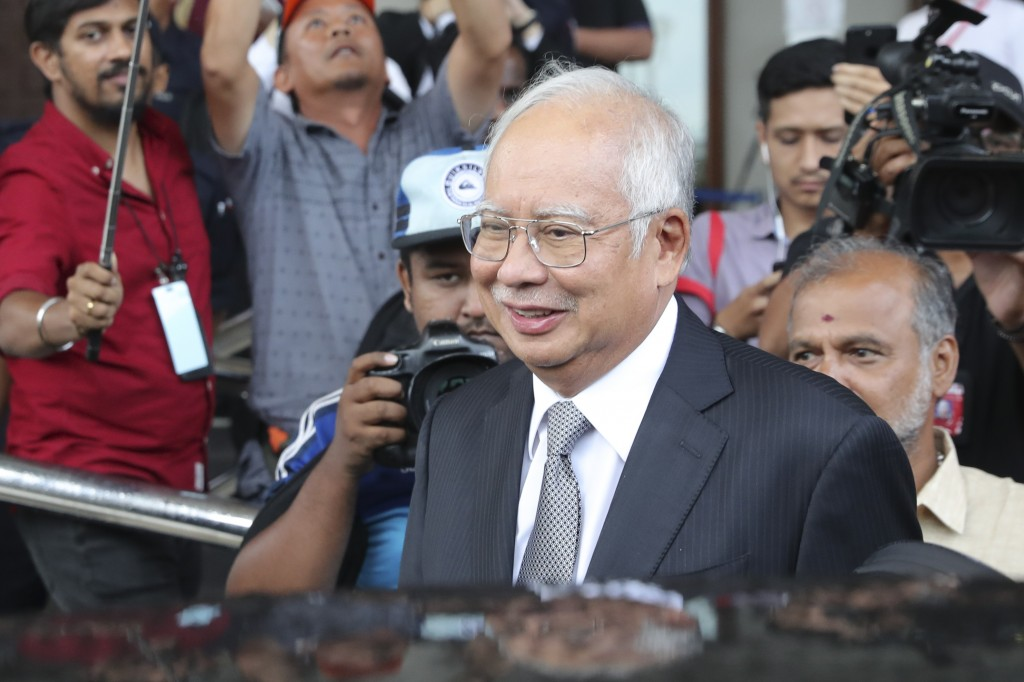 Malaysia's former Prime Minister Najib Razak, center, gets into a car after his court appearance at the Kuala Lumpur High Court in Kuala Lumpur, Malay