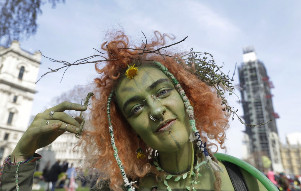 A woman dressed as a wood nymph during a climate protest in Parliament Square in London, Monday, April 15, 2019. Extinction Rebellion have organised a