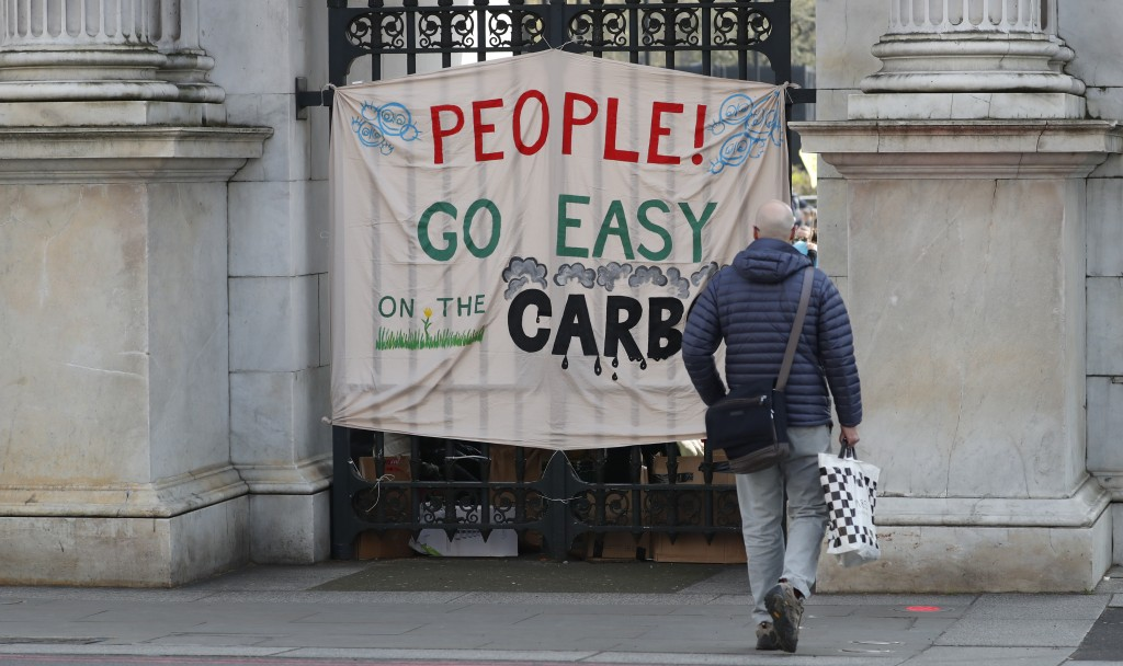 A tourist looks at a climate change protest banner at Marble Arch in London, Monday, April 15, 2019. Extinction Rebellion have organised a nationwide