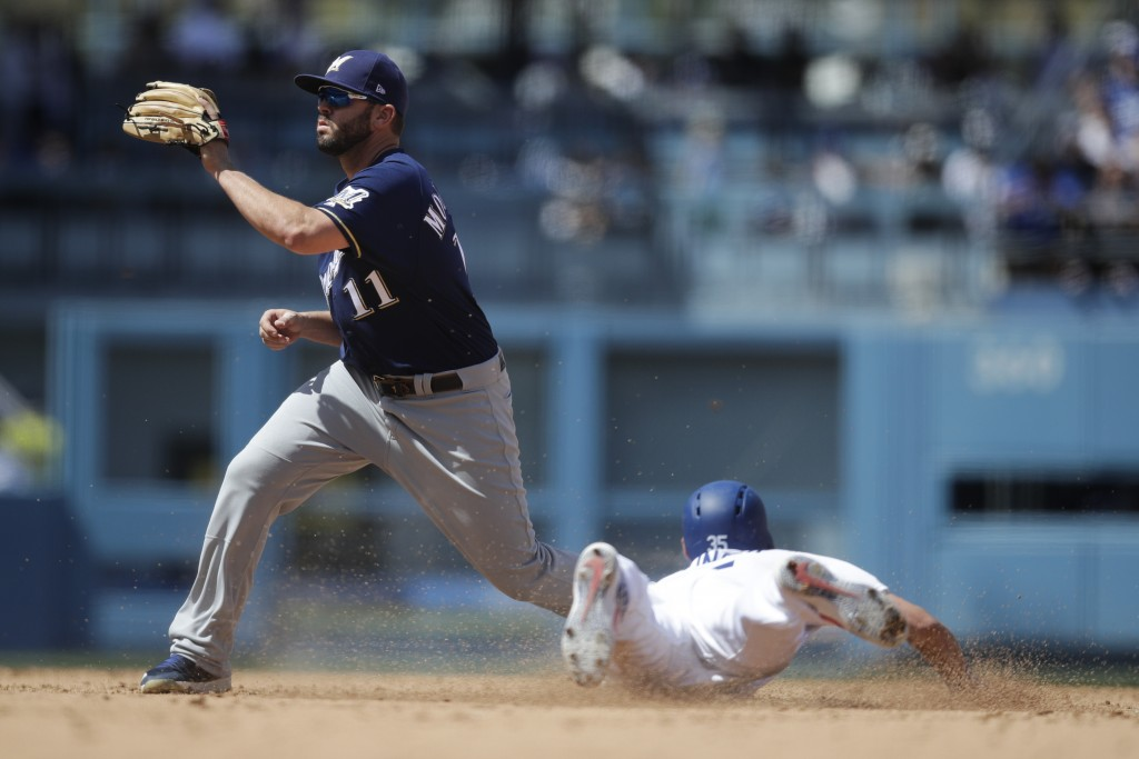 Los Angeles Dodgers' Cody Bellinger, right, steals second base as Milwaukee Brewers' Mike Moustakas waits for the throw during the fourth inning of a