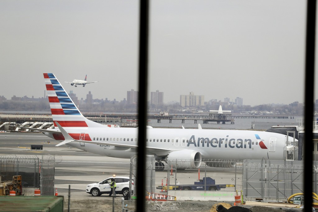 FILE - In a March 13, 2019 file photo, an American Airlines Boeing 737 MAX 8 sits at a boarding gate at LaGuardia Airport in New York. American Airlin