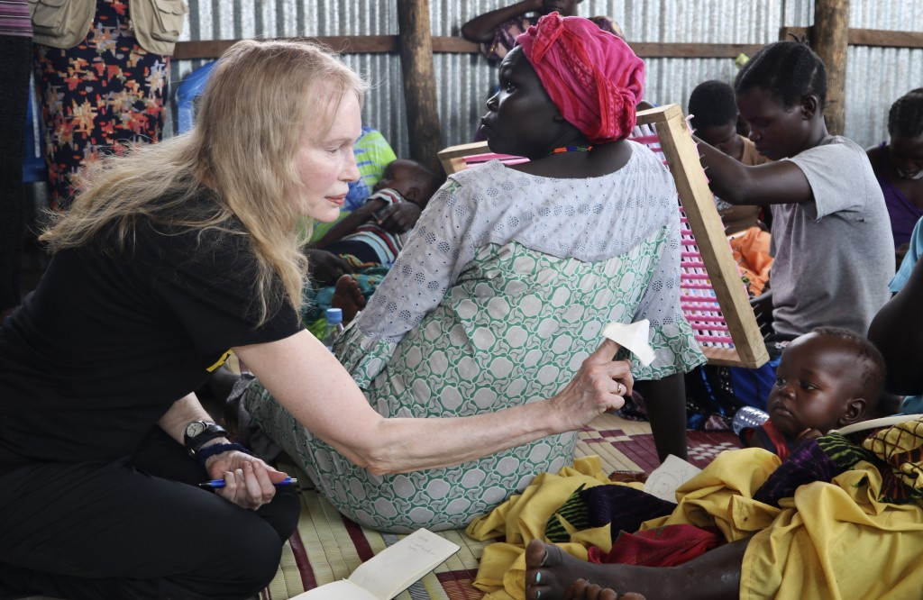In this photo taken Tuesday, April 2, 2019, human rights activist Mia Farrow plays with a baby lying on his mother's lap while speaking to a group of