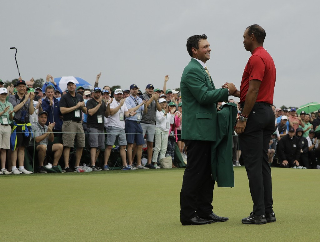 Patrick Reed helps Tiger Woods with his green jacket after Woods won the Masters golf tournament Sunday, April 14, 2019, in Augusta, Ga. (AP Photo/Cha