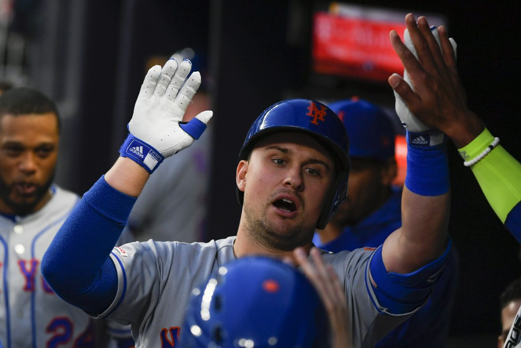 New York Mets' J.D. Davis is congratulated in the dugout after hitting a home run to center field during the second inning of a baseball game against