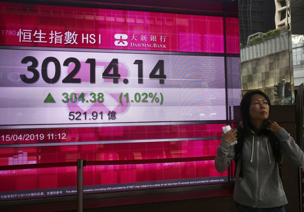 A woman walks past an electronic board showing Hong Kong share index outside a local bank in Hong Kong, Monday, April 15, 2019.  Asian markets were br