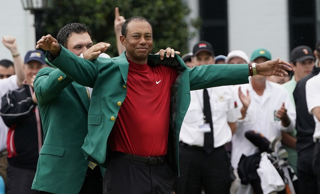 Patrick Reed helps Tiger Woods with his green jacket after Woods won the Masters golf tournament Sunday, April 14, 2019, in Augusta, Ga. (AP Photo/Dav