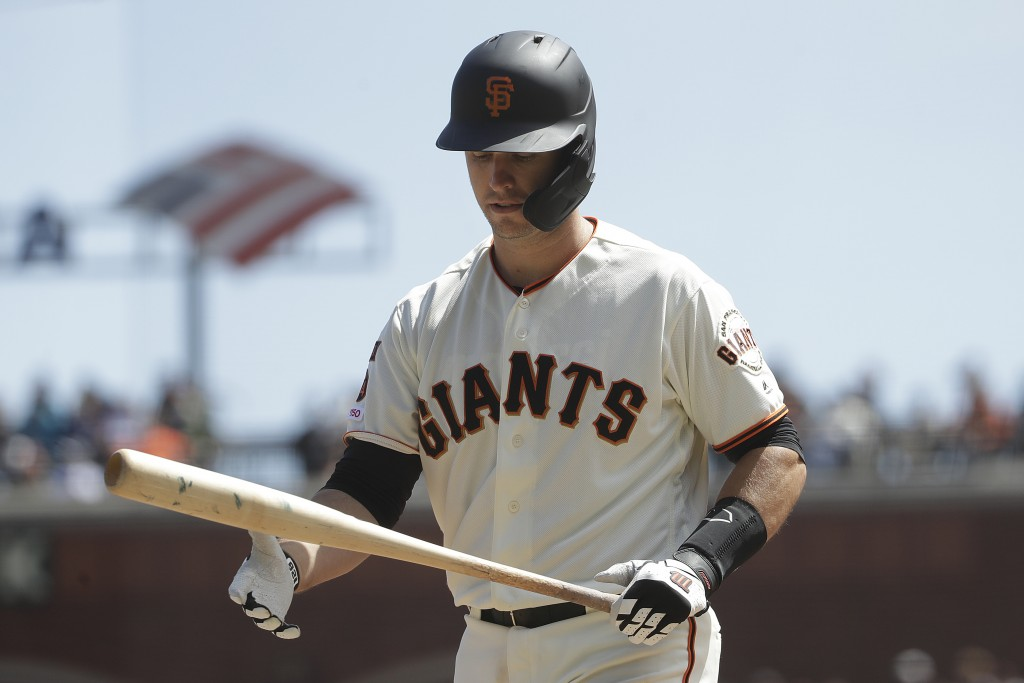 San Francisco Giants' Buster Posey walks to the dugout after striking out against the Colorado Rockies during the fourth inning of a baseball game in