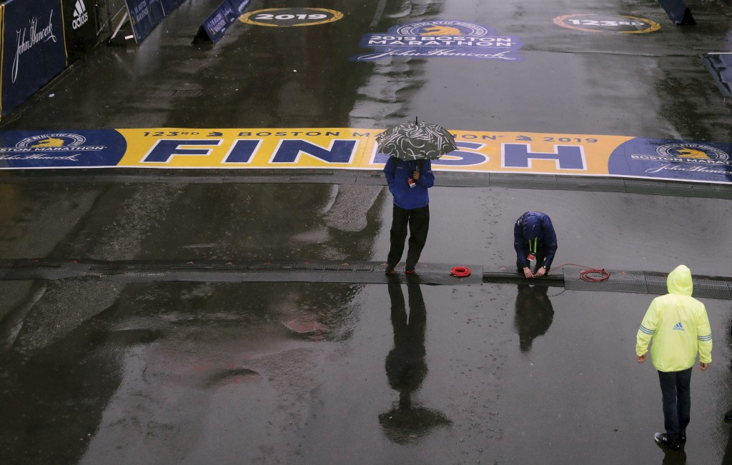 Final preparations are made in the rain at the finish line for the 123rd Boston Marathon on Monday, April 15, 2019, in Boston. (AP Photo/Charles Krupa