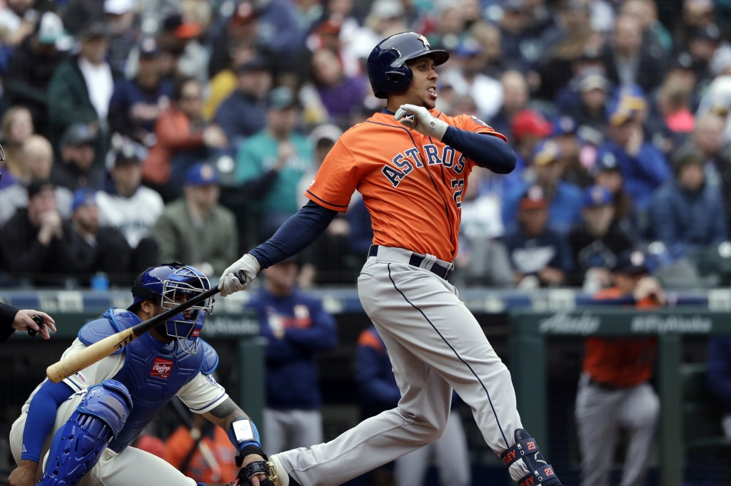 Houston Astros' Michael Brantley, right, and Seattle Mariners catcher Omar Narvaez watch the path of Brantley's two-run single in the sixth inning of