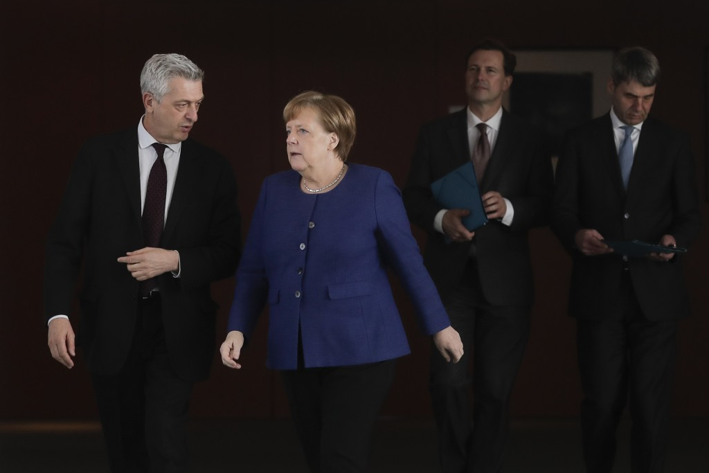 German Chancellor Angela Merkel, second from left, welcomes United Nations High Commissioner for Refugees Filippo Grandi, left, for a meeting at the c