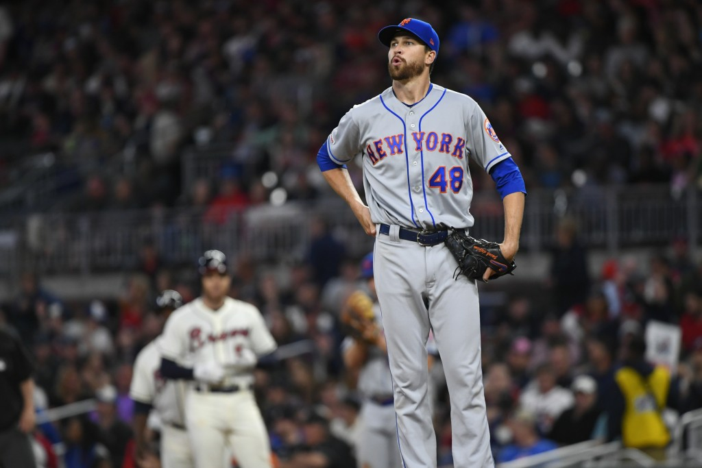 New York Mets' Jacob deGrom (48) takes a deep breath after walking Atlanta Braves Freddie Freeman, left, during the third inning of a baseball game Su