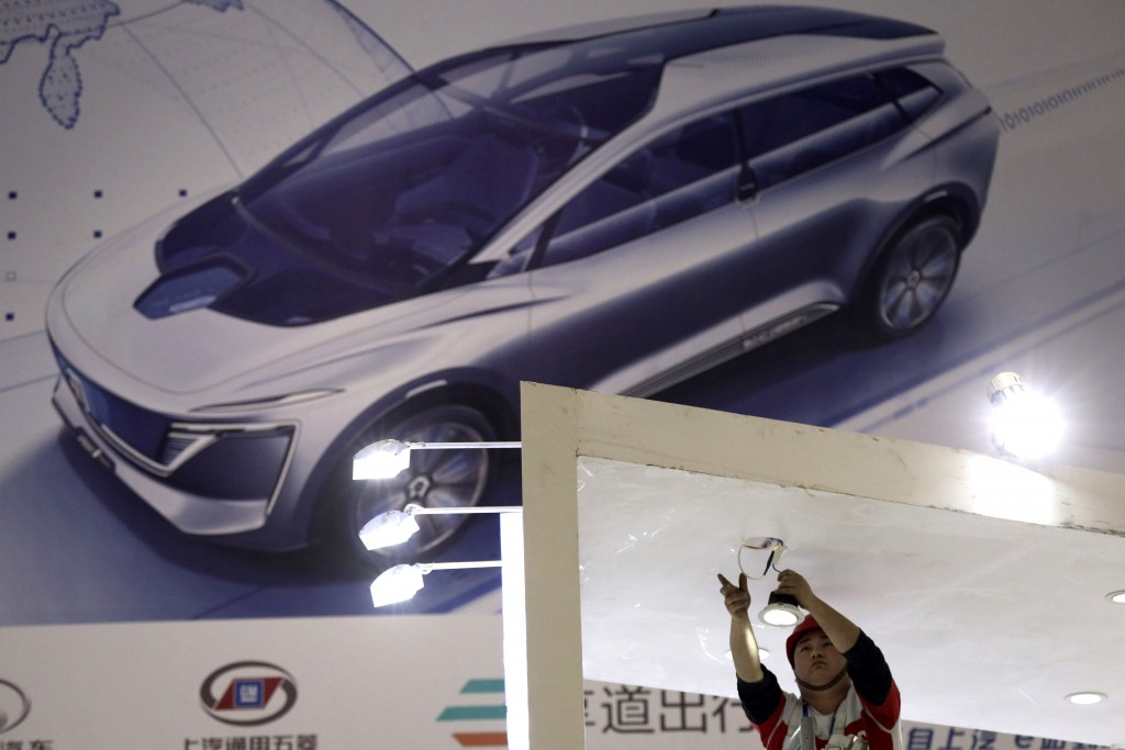 A worker installs lightings before the start of the Auto Shanghai 2019 show in Shanghai on Monday, April 15, 2019. This year's Shanghai auto show whic