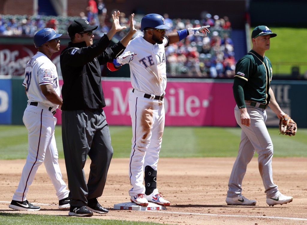 Texas Rangers' Elvis Andrus stands on third celebrating his run-scoring triple as base coach Tony Beasley, umpire Jansen Visconti and Oakland Athletic...